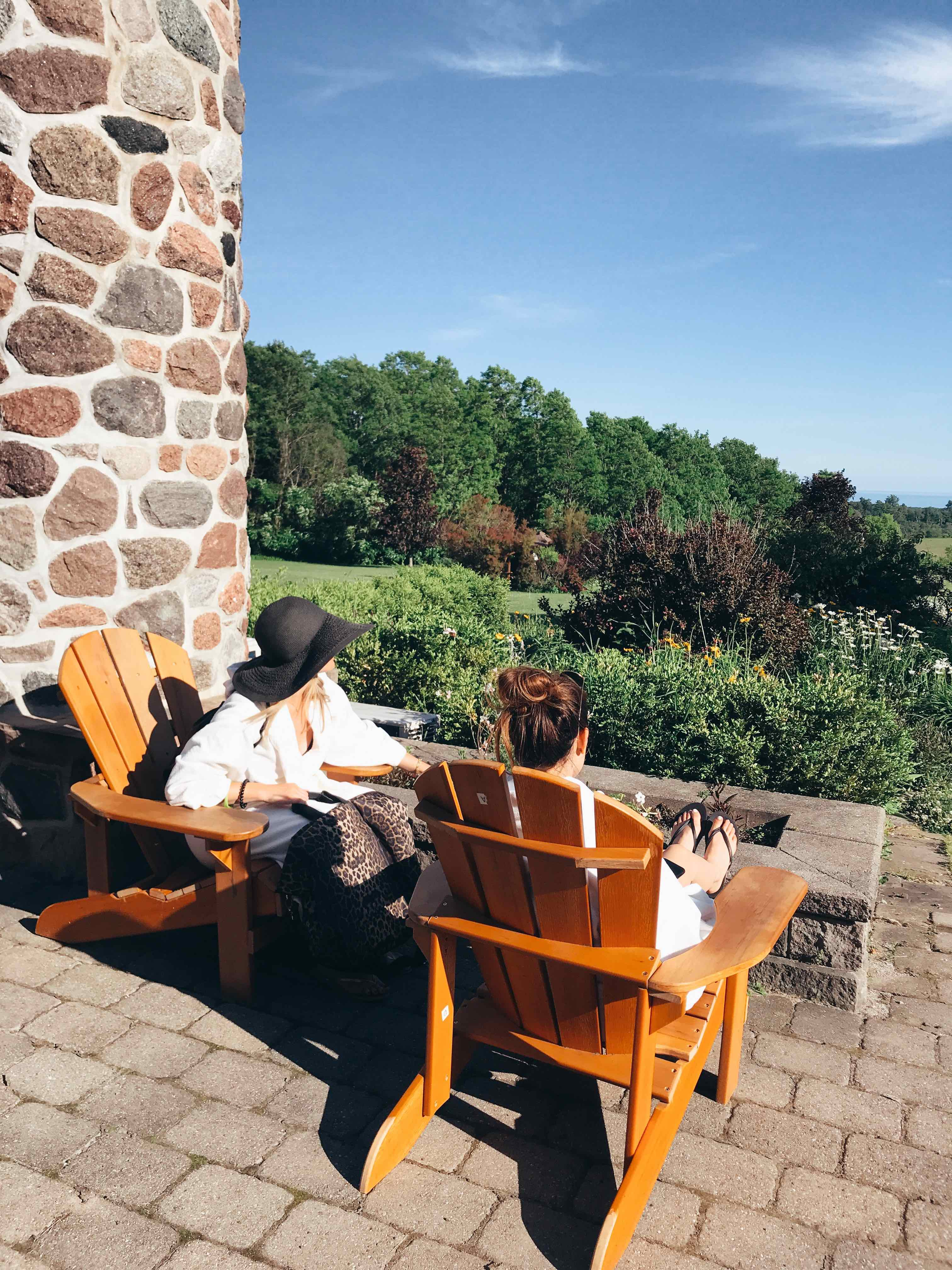 two women at ste annes spa sitting on orange lawn chairs looking at the trees and scenery